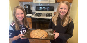 Girls holding a pan of scones